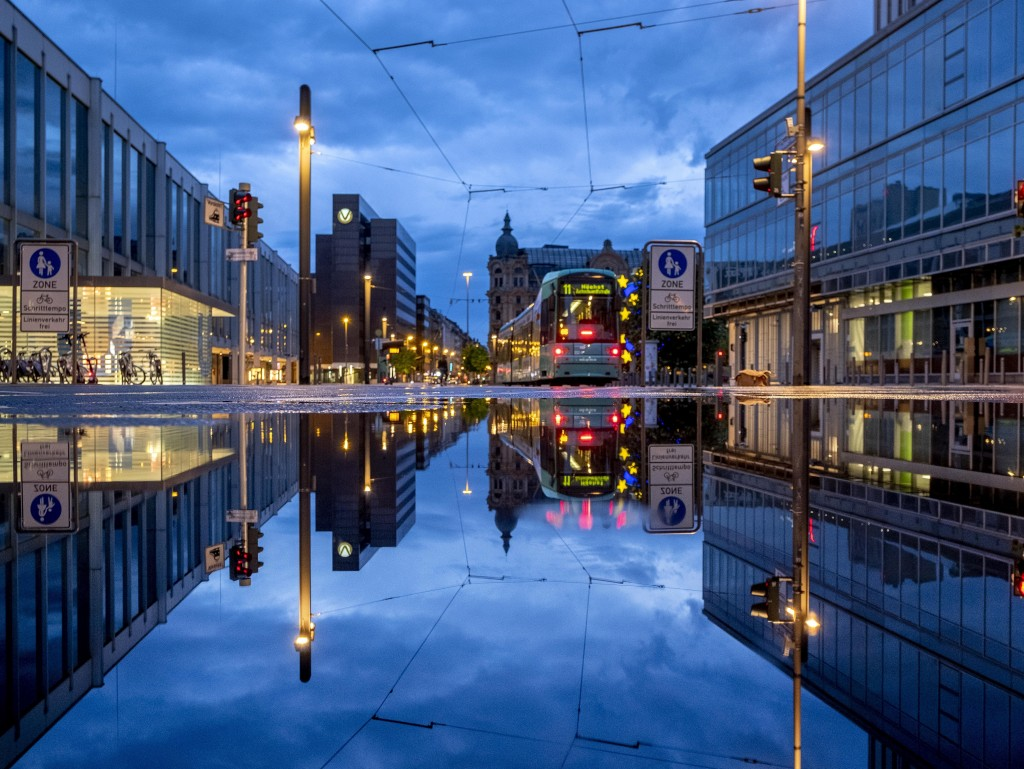 A tram is reflected in a puddle after the city is almost empty shortly after the end of the curfew in central Frankfurt, Germany, Tuesday, May 11, 202...