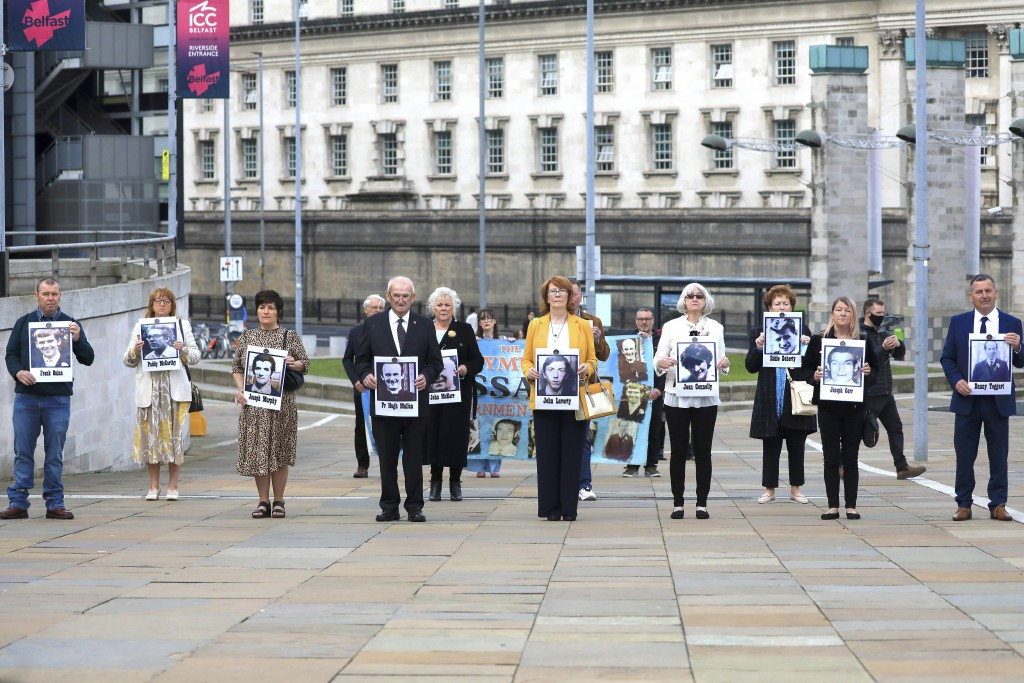 Family members arrive for the inquest into holding photos of the victims of the Ballymurphy shooting, in Belfast, Northern Ireland, Tuesday May 11, 20...