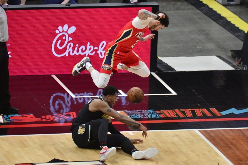 New Orleans Pelicans guard Lonzo Ball (2) jumps to avoid Memphis Grizzlies center Xavier Tillman in the second half of an NBA basketball game Monday, ...