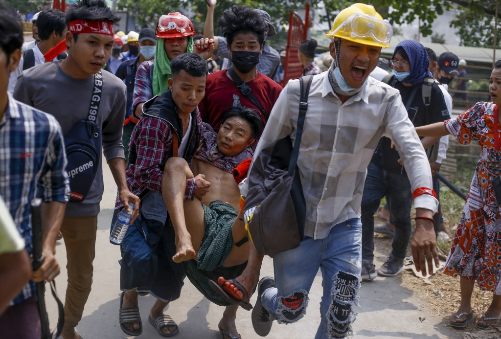 FILE - In this March 14, 2021, file photo, anti-coup protesters carry an injured man following clashes with security in Yangon, Myanmar. The military ...
