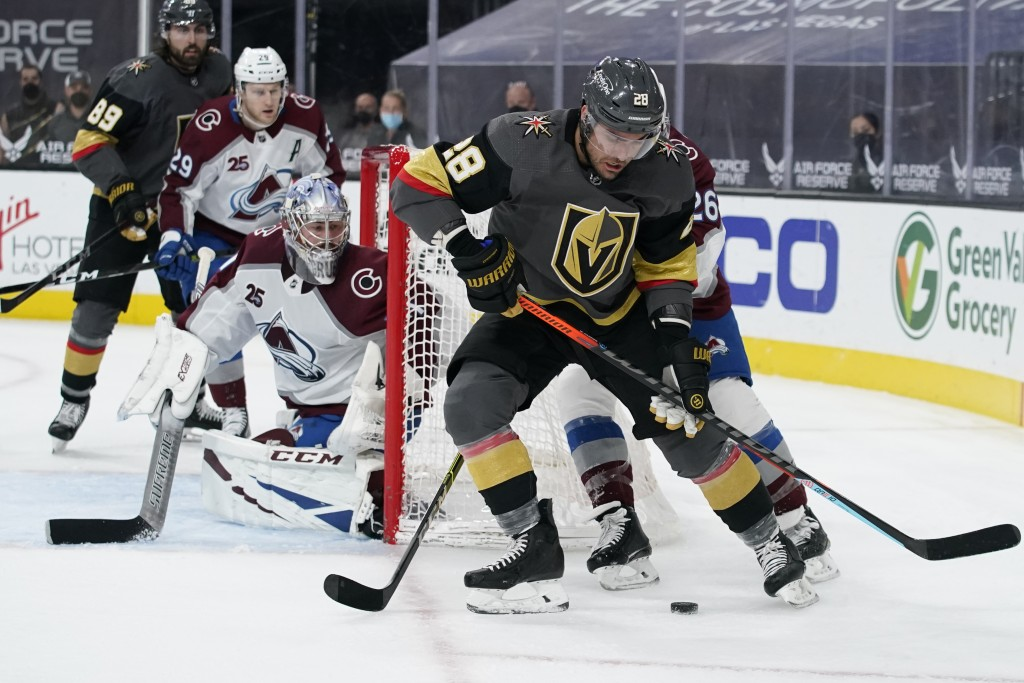 Vegas Golden Knights left wing William Carrier (28) skates around Colorado Avalanche defenseman Jacob MacDonald (26) during the second period of an NH...