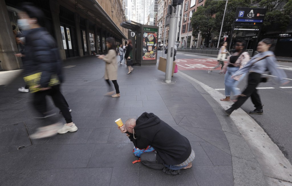 A man, center, panhandles for money on a corner in Sydney, Tuesday, May 11, 2021, as the government prepares to release its big-spending economic plan...