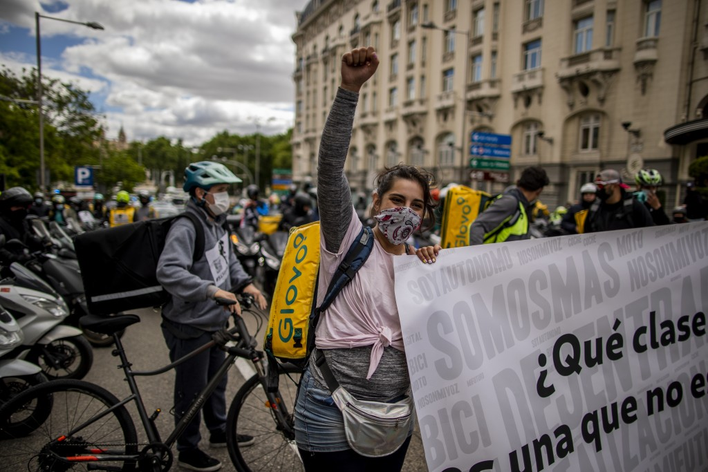 Delivery workers protest in front of the Spanish Parliament in Madrid, Spain, Tuesday, May 11, 2021. Spain has approved a pioneering law that gives de...