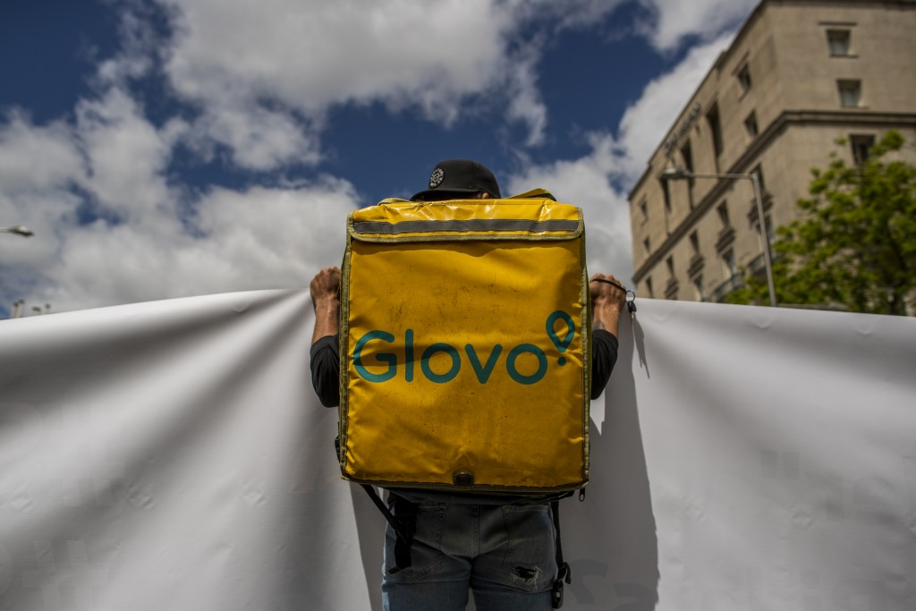 A delivery worker protests in front of the Spanish Parliament in Madrid, Spain, Tuesday, May 11, 2021. Spain has approved a pioneering law that gives ...