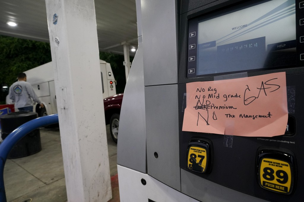 A hand written sign is posted on a gas pump, showing that the service station is out of all grades of fuel Wednesday, May 12, 2021, in Charlotte, N.C....