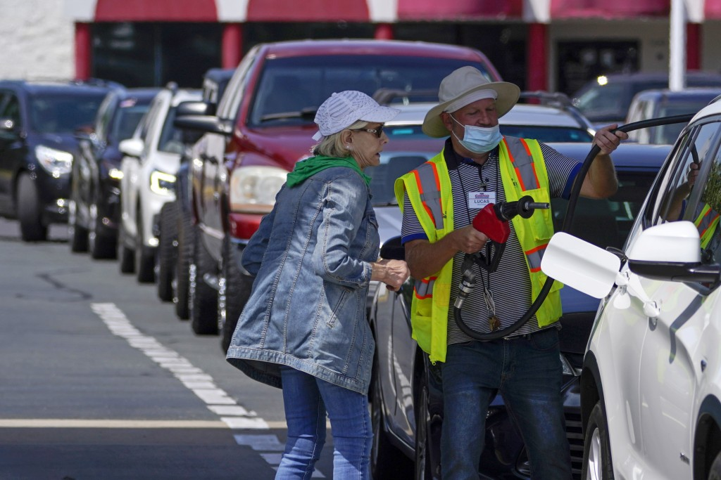 A customer helps pumping gas at Costco, as other wait in line, on Tuesday, May 11, 2021, in Charlotte, N.C. Colonial Pipeline, which delivers about 45...