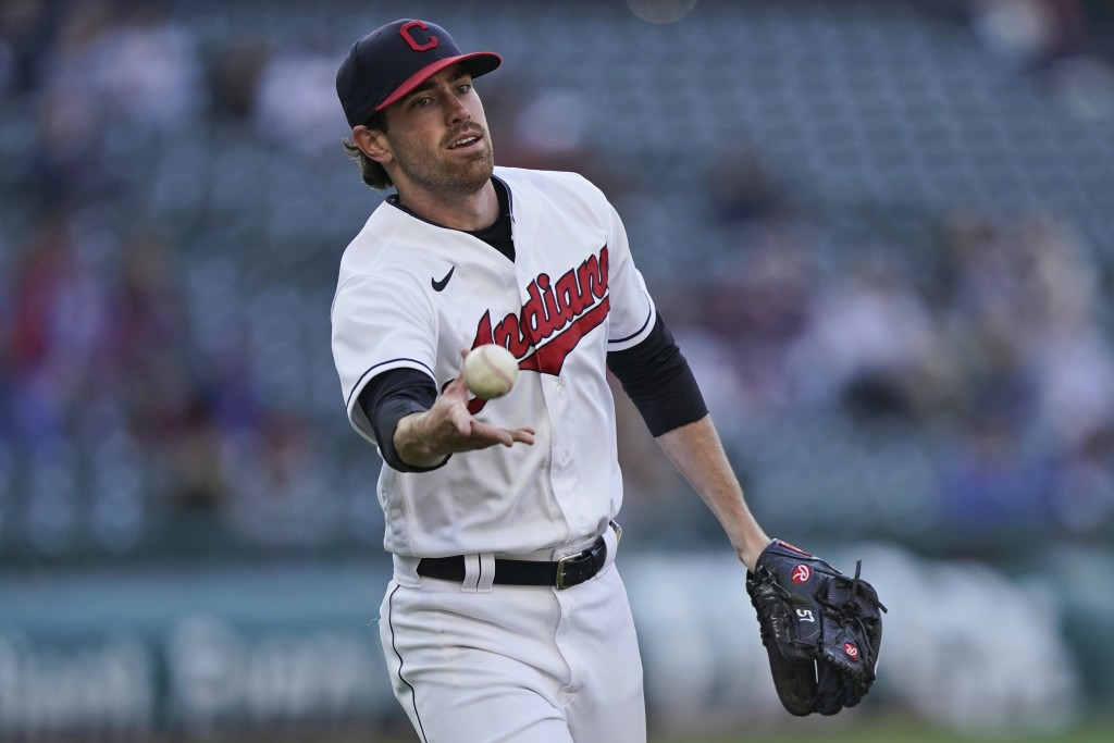 Cleveland Indians starting pitcher Shane Bieber tosses the ball to first base to get Chicago Cubs' Joc Pederson out in the third inning of a baseball ...