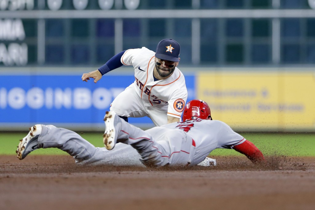 Houston Astros second baseman Jose Altuve, left, makes the tag for the out on Los Angeles Angels third baseman Taylor Ward, right, on his attempted st...