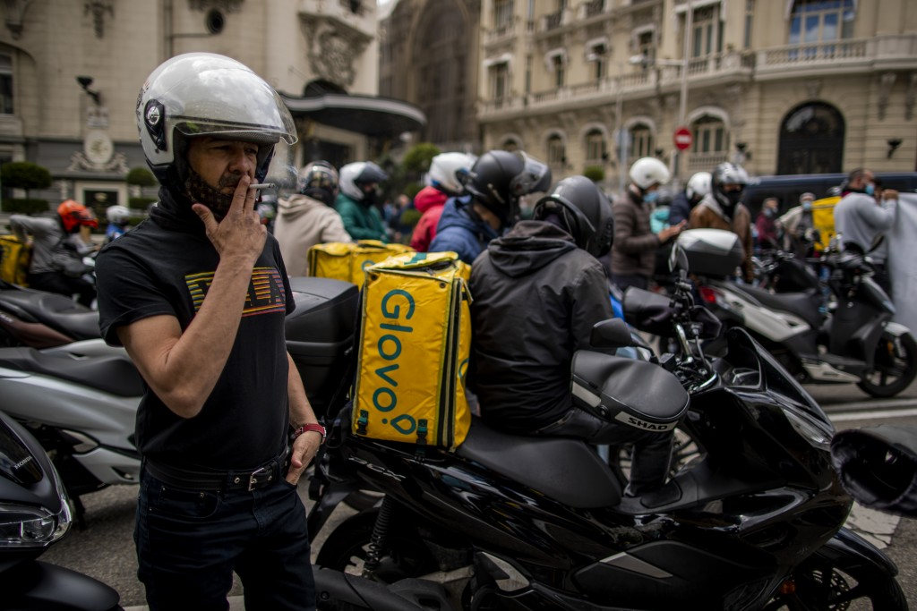 Delivery workers gather during a protest in front of the Spanish Parliament in Madrid, Spain, Tuesday, May 11, 2021. Spain has approved a pioneering l...