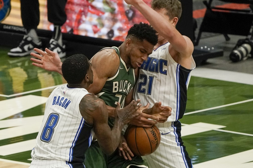 Milwaukee Bucks' Giannis Antetokounmpo battles for a loose ball with Orlando Magic's Dwayne Bacon and Moritz Wagner during the second half of an NBA b...