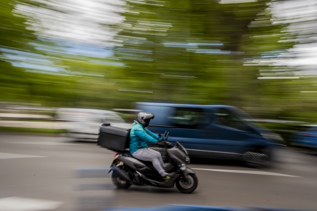 A delivery worker rides his motorbike in Madrid, Spain, Tuesday, May 11, 2021. Spain has approved a pioneering law that gives delivery platforms a mid...