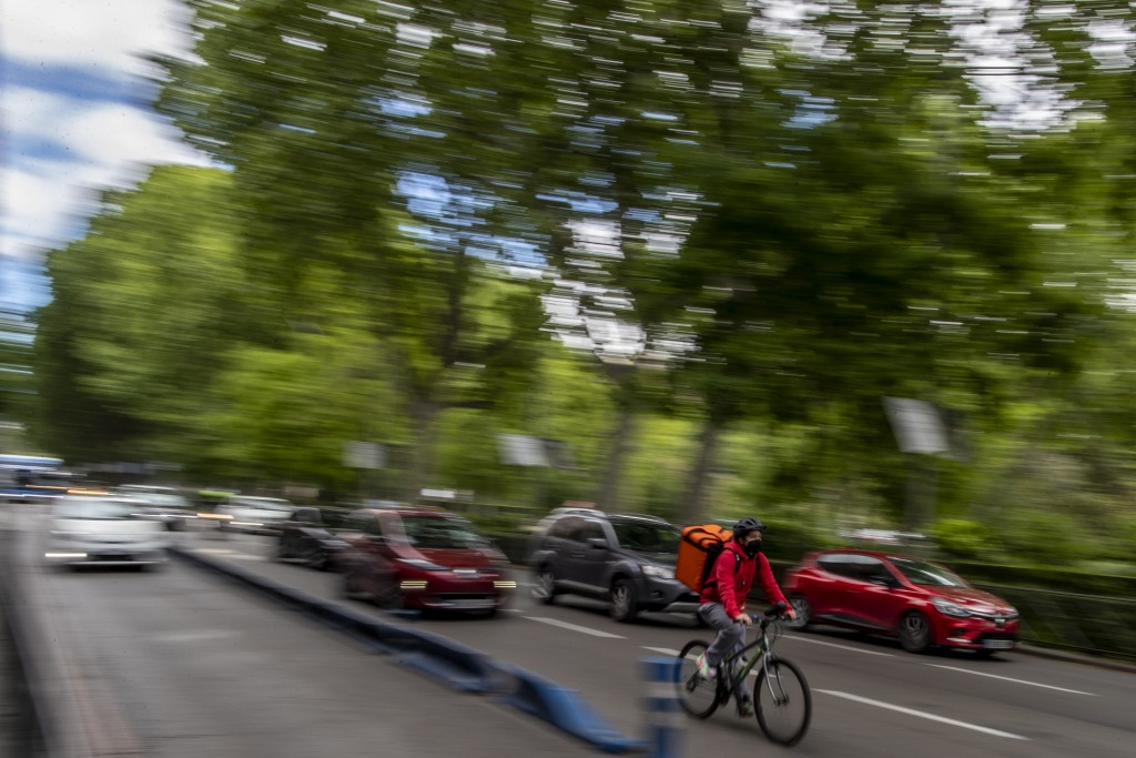 A delivery worker rides his bike in Madrid, Spain, Tuesday, May 11, 2021. Spain has approved a pioneering law that gives delivery platforms a mid-Augu...