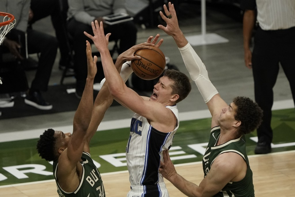 Orlando Magic's Moritz Wagner is fouled as he shoots between Milwaukee Bucks' Giannis Antetokounmpo and Brook Lopez during the second half of an NBA b...