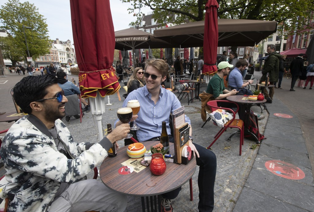 FILE - In this Wednesday, April 28, 2021 file photo, people toast after terraces reopened at midday as the Netherlands became the latest European coun...