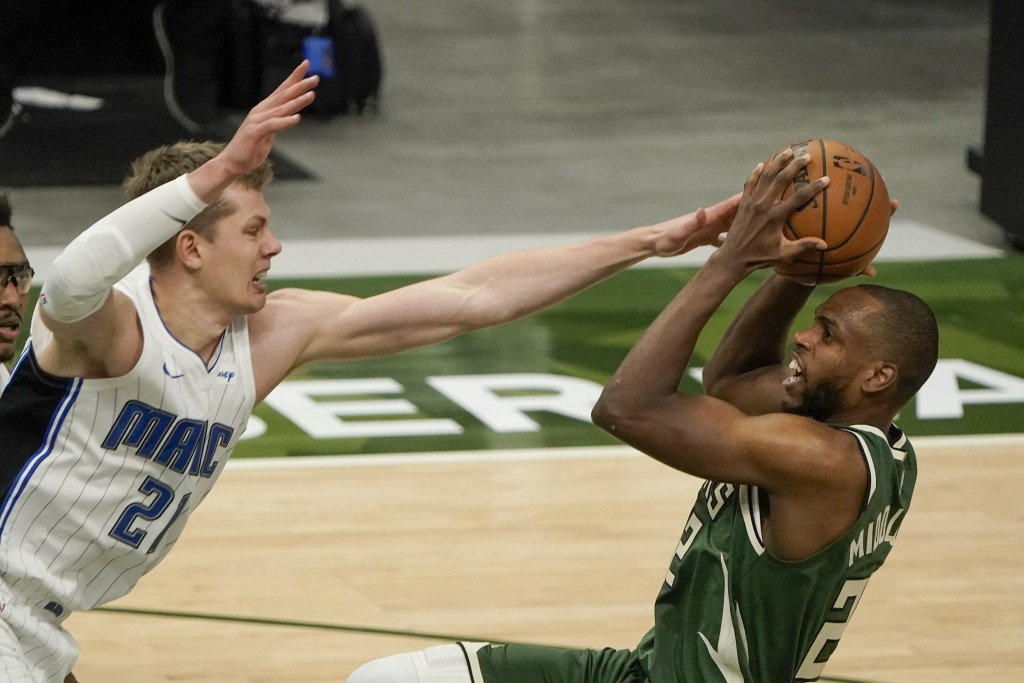 Milwaukee Bucks' Khris Middleton shoots over Orlando Magic's Moritz Wagner during the first half of an NBA basketball game Tuesday, May 11, 2021, in M...