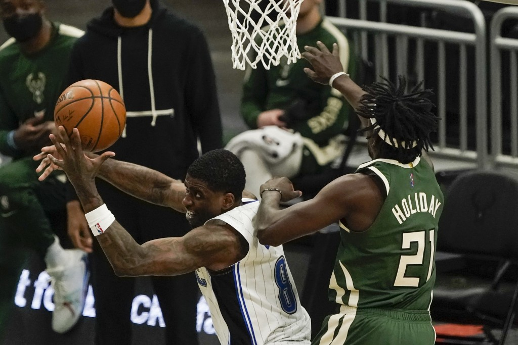Orlando Magic's Dwayne Bacon tries to shoot past Milwaukee Bucks' Jrue Holiday during the second half of an NBA basketball game Tuesday, May 11, 2021,...