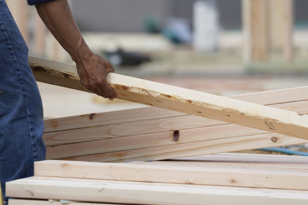 A workman arranges a beam on a frame at a new housing site in Madison County, Miss., Tuesday, March 16, 2021. Rising prices for a variety of commoditi...