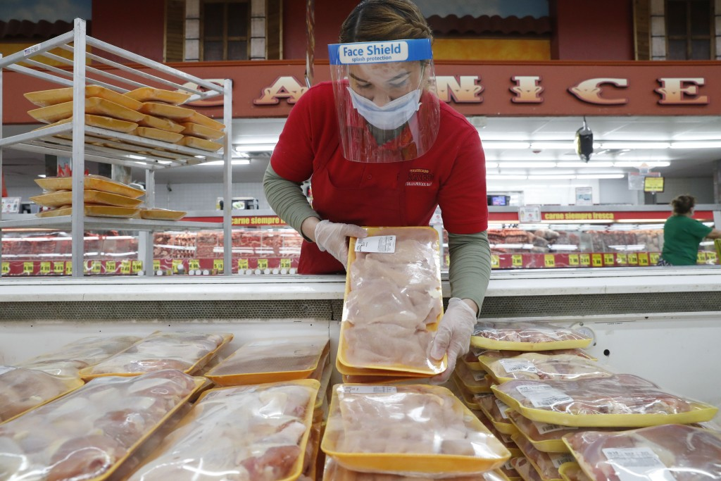 FILE - In this April 29, 2020 file photo, a worker restocks chicken in the meat product section at a grocery store in Dallas. Rising prices for a vari...