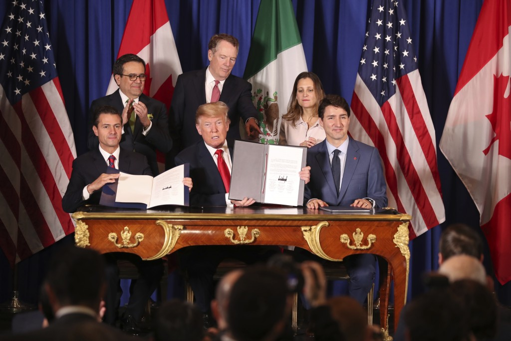 FILE - In this Nov. 30, 2018 file photo, President Donald Trump, center, sits between Canada's Prime Minister Justin Trudeau, right, and Mexico's Pres...