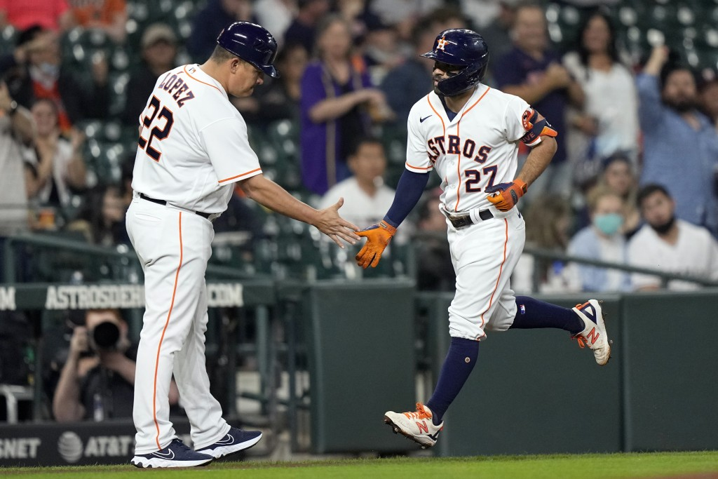Houston Astros' Jose Altuve (27) is congratulated by first base coach Omar Lopez (22) after hitting a home run against the Los Angeles Angels during t...