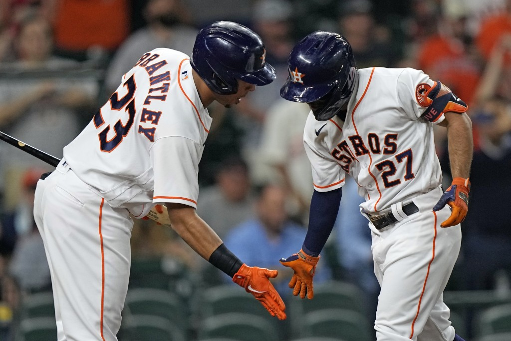 Houston Astros' Jose Altuve (27) is congratulated by Michael Brantley (23) after hitting a home run against the Los Angeles Angels during the first in...