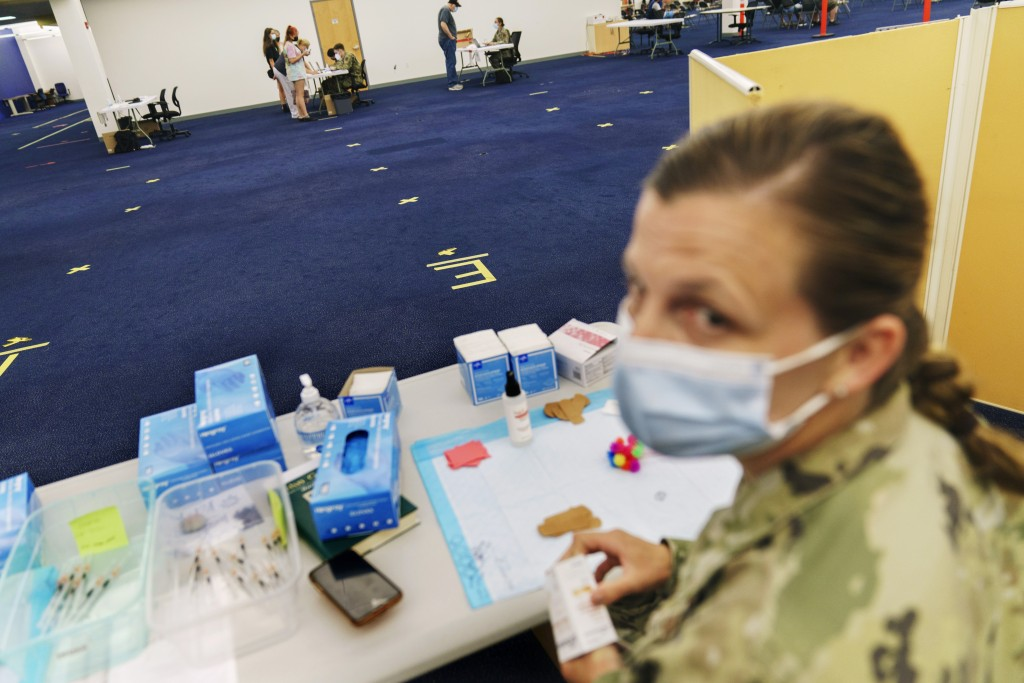 Tape on the floor marks where a line would normally form for people arriving for their COVID-19 inoculation as U.S. Air National Guard Capt. Jennifer ...