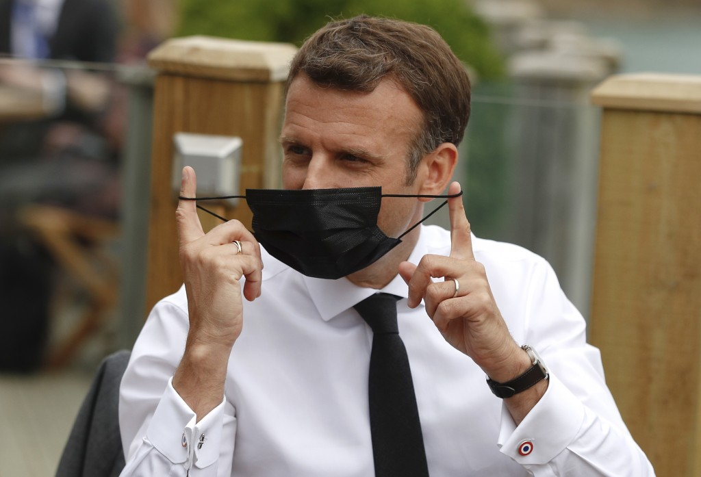 French President Emmanuel Macron takes off his protective face mask as he waits for the start of an EU coordination meeting at the G7 meeting at the C...