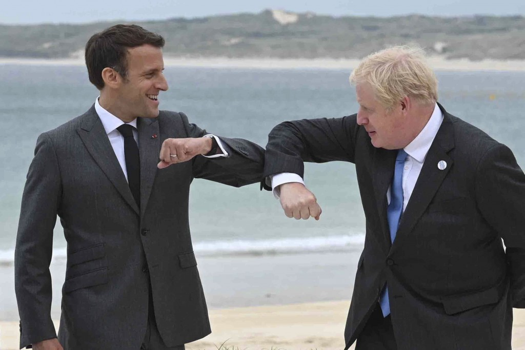 Britain's Prime Minister Boris Johnson, right greets French President Emmanuel Macron prior to the Leaders official welcome and group photo session, d...