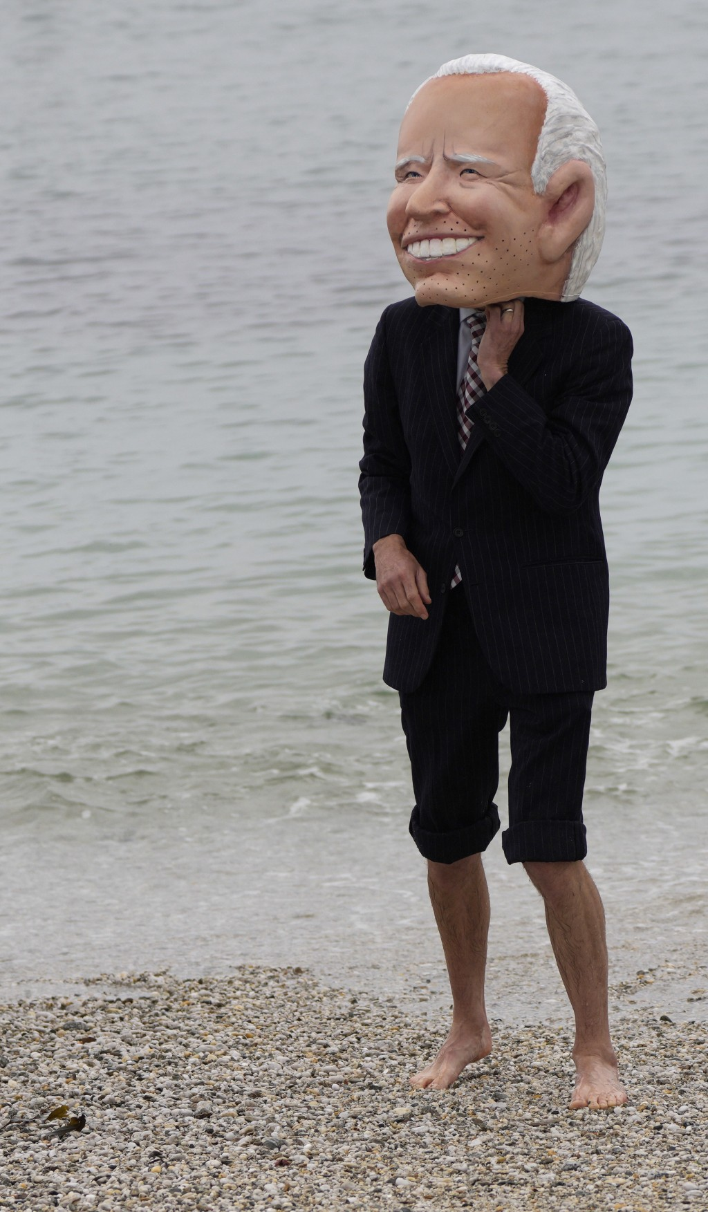 An activist wearing a giant head of G7 leader U.S. President Joe Biden walks on the beach prior to an action regarding COVID-19 vaccines on Swanpool B...