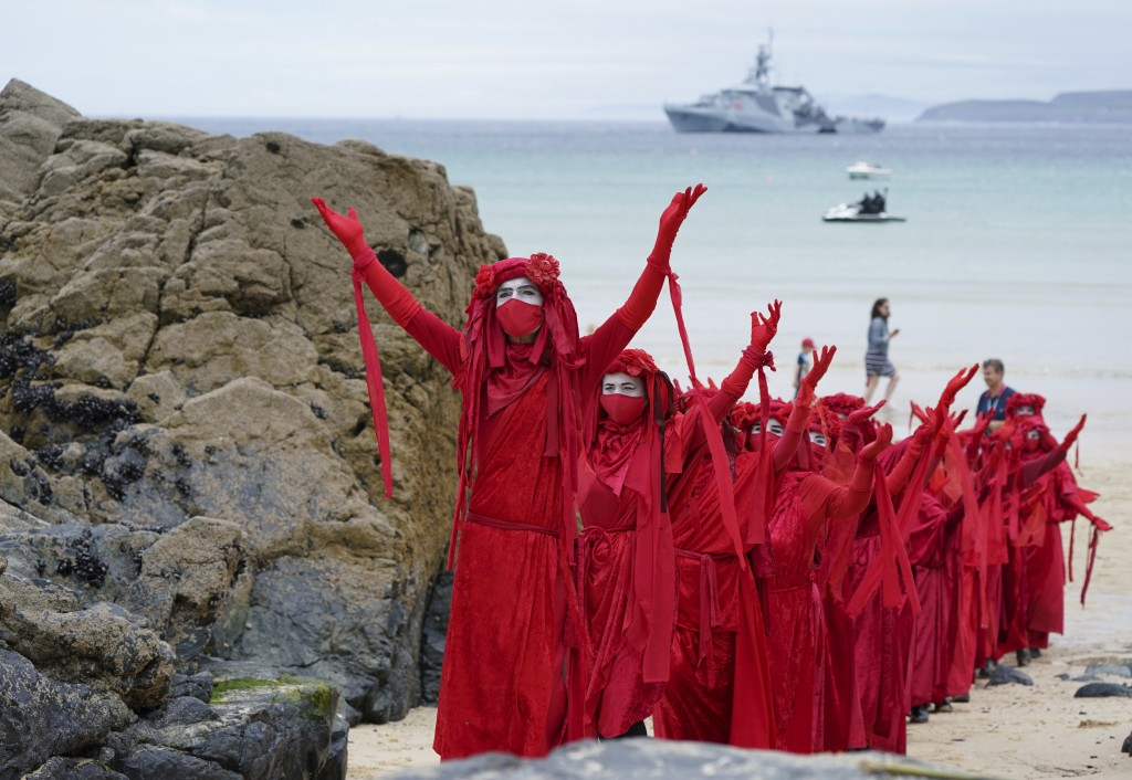 Protestors in costumes march on the beach of Carbis Bay outside the G7 meeting taking place in St. Ives, Cornwall, England, Friday, June 11, 2021. Lea...