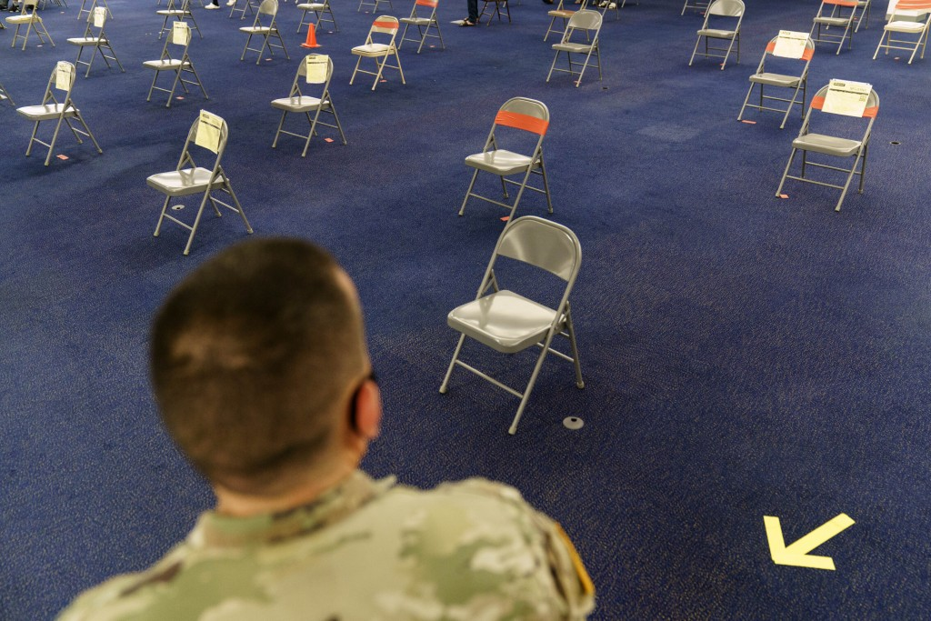 Rhode Island Army National Guard Sgt. Juan Gomez looks over the post inoculation waiting area at a coronavirus mass-vaccination site at the former Cit...