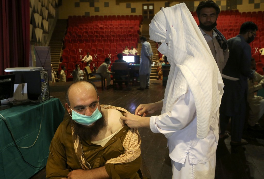 A government employee receives the Convidecia COVID-19 vaccine from a paramedic at a vaccination center in Nishtar hall, in Peshawar, Pakistan, Friday...