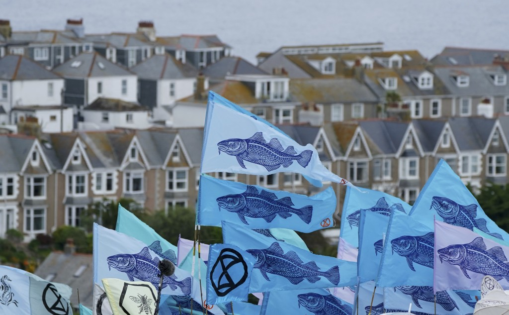 Protestors wave flags during a demonstration near the G7 meeting taking place in St. Ives, Cornwall, England, Friday, June 11, 2021. Leaders of the G7...