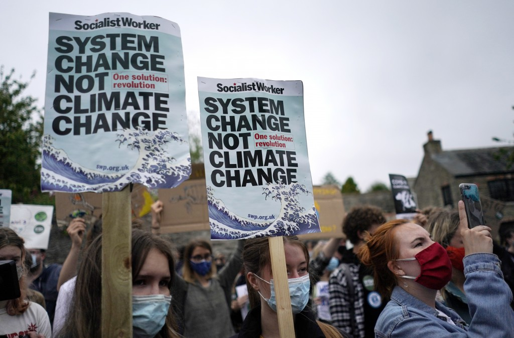 Climate activists wave signs and chant as they march during a demonstration taking place outside a meeting of G7 leaders in Falmouth, Cornwall, Englan...