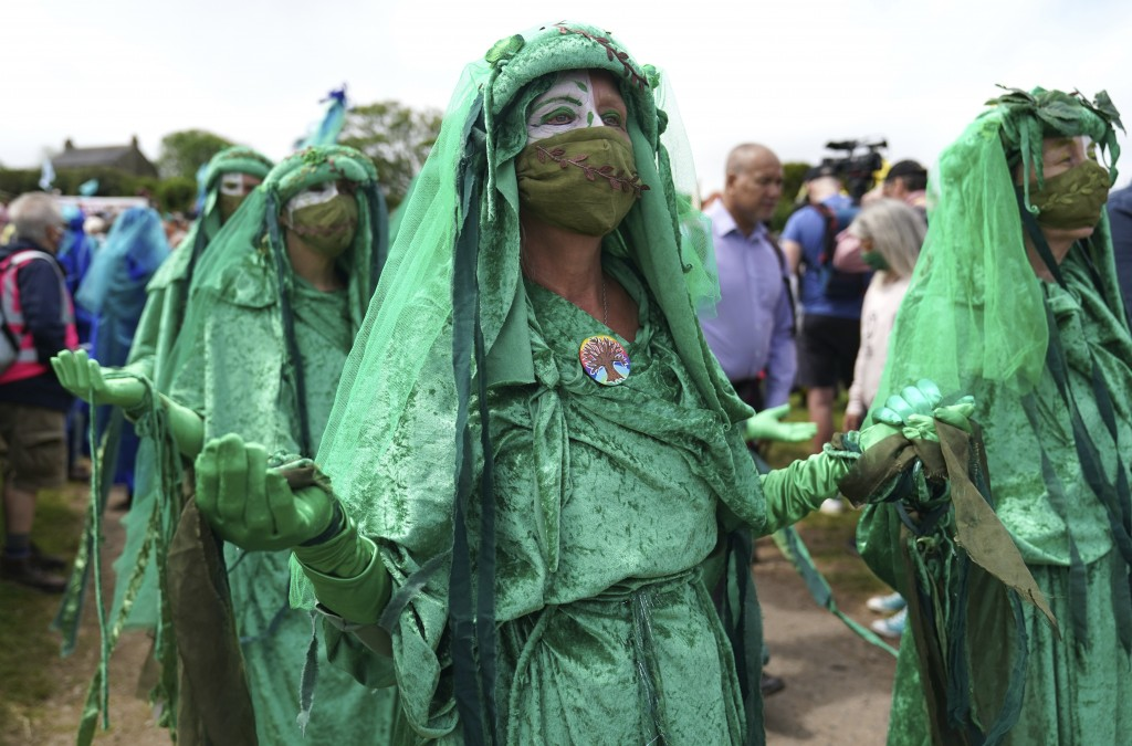 Climate activists are dressed in costumes as they demonstrate near the G7 meeting taking place in St. Ives, Cornwall, England, Friday, June 11, 2021. ...