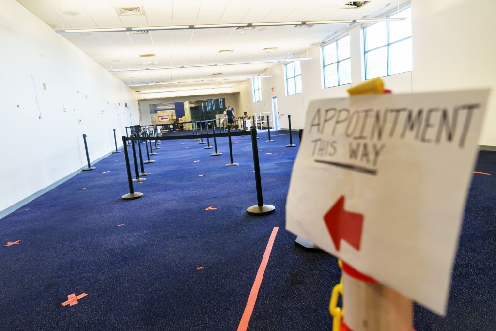 A sign points the way to a check-in area at a coronavirus mass-vaccination site at the former Citizens Bank headquarters in Cranston, R.I., Thursday, ...