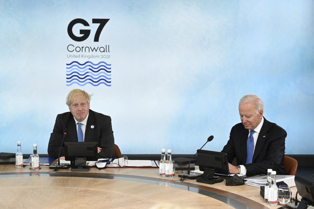 British Prime Minister Boris Johnson, left and US President Joe Biden sit around the table at the top of the G7 meeting, in Carbis Bay, Cornwall, Engl...