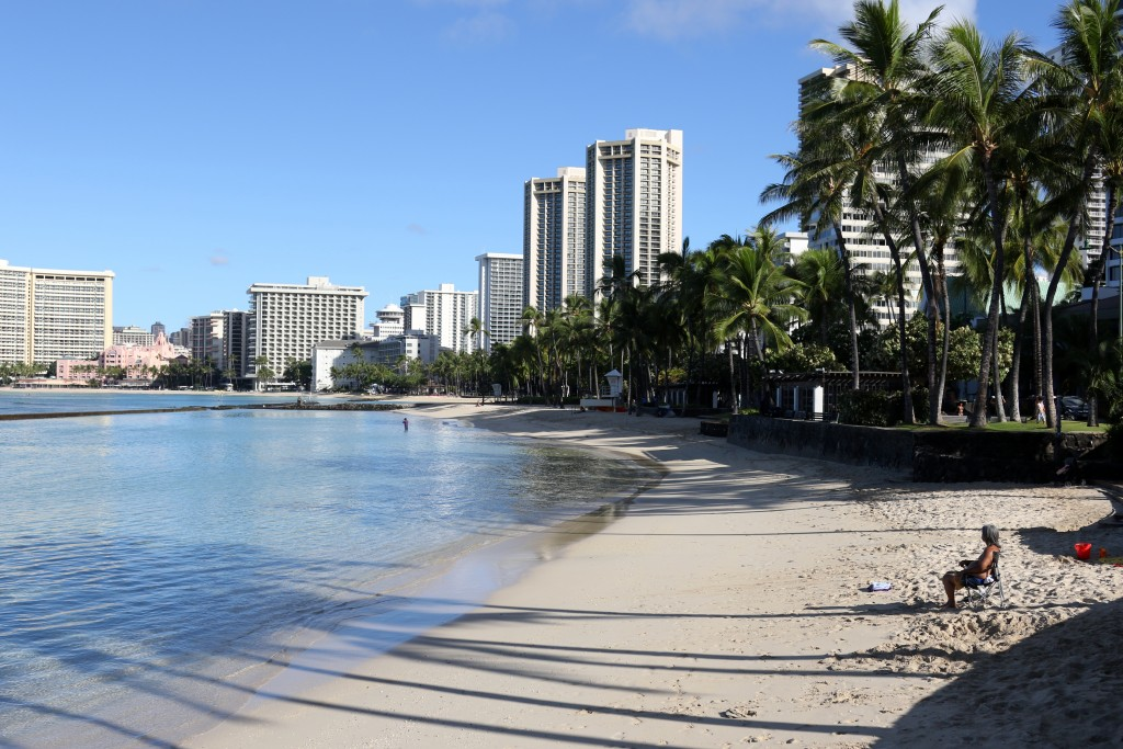 FILE - In this Oct. 2, 2020, file photo, a man sits on Waikiki Beach in Honolulu. Honolulu is loosening some restrictions on social activity now that ...