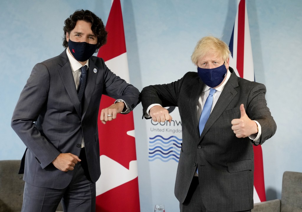 British Prime Minister Boris Johnson, right, greets Canadian Prime Minister Justin Trudeau with an elbow bump prior to a bilateral meeting during the ...