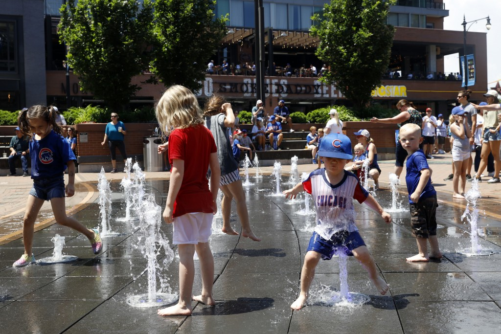 Kids play around a water fountain outside of Chicago's Wrigley Field before a baseball game, Friday, June 11, 2021, as Chicago and rest of Illinois fu...