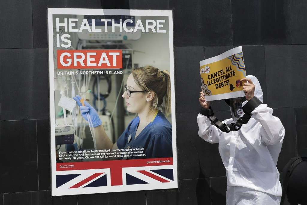 A protester dressed in a protective suit holds slogans during a rally against the G7 summit outside the British Embassy in Taguig, Philippines on Frid...