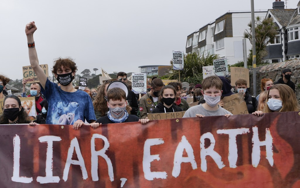 Climate activists hold a banner while marching as they demonstrate as part of Fridays for Future in Falmouth, Cornwall, England, Friday, June 11, 2021...