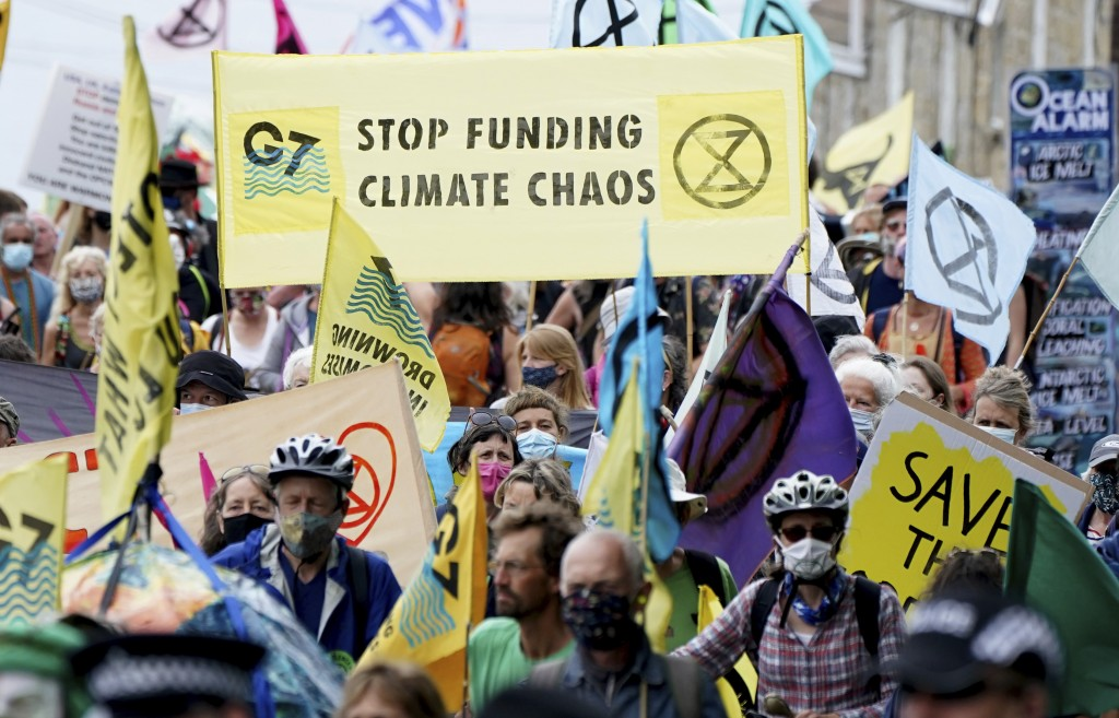 Climate activists and others wave banners and flags as they demonstrate near the G7 meeting taking place in St. Ives, Cornwall, England, Friday, June ...