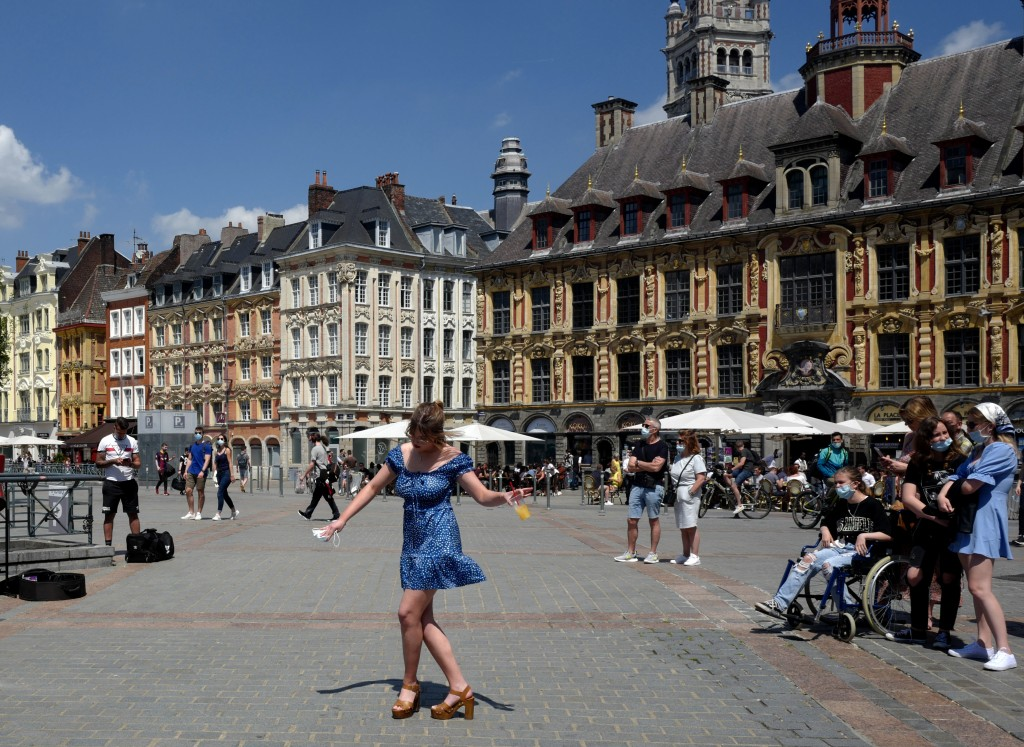 FILE - In this June 6, 2021 file photo, a woman dances by a cafe terrace in Lille, northern France. France is lifting mandatory mask-wearing outdoors ...