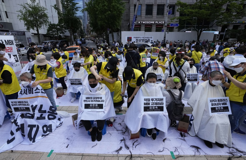 Workers wearing face masks to help protect against the spread of the coronavirus shave their heads during a rally demanding job security in Seoul, Sou...