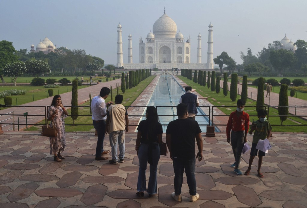 FILE - In this Sept. 21, 2020, file photo, a small number of tourists visit as the Taj Mahal monument in Agra, India. India is reopening yet again its...