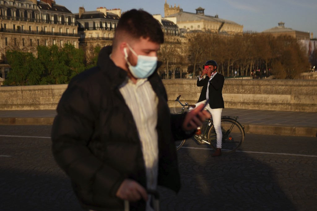 FILE - In this March 29, 2021 file photo, A man walks with a face mask to prevent the spread of the COVID-19 coronavirus, as a man takes a snapshot of...