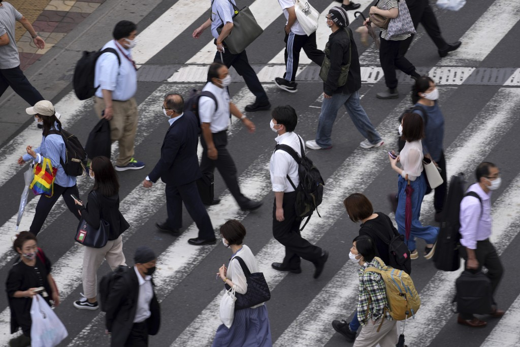 People wearing protective masks to help curb the spread of the coronavirus walk along a pedestrian crossing Wednesday, June 16, 2021, in Tokyo. The Ja...
