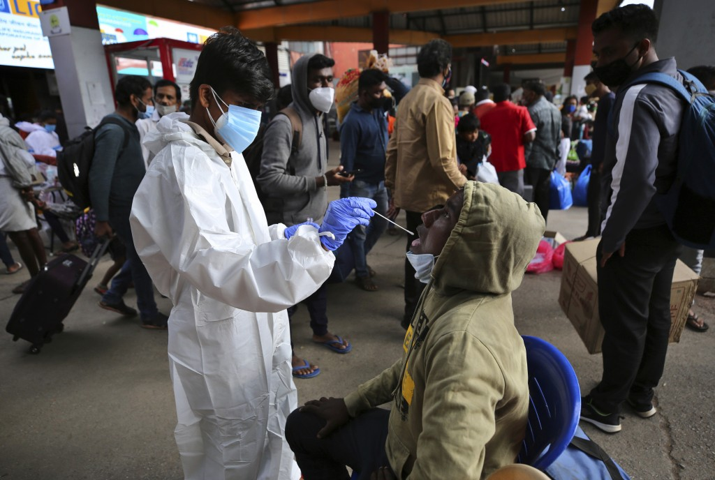 A health worker in protective suit collects a swab sample of a traveler to test for COVID-19 outside a train station in Bengaluru, India, Wednesday, J...