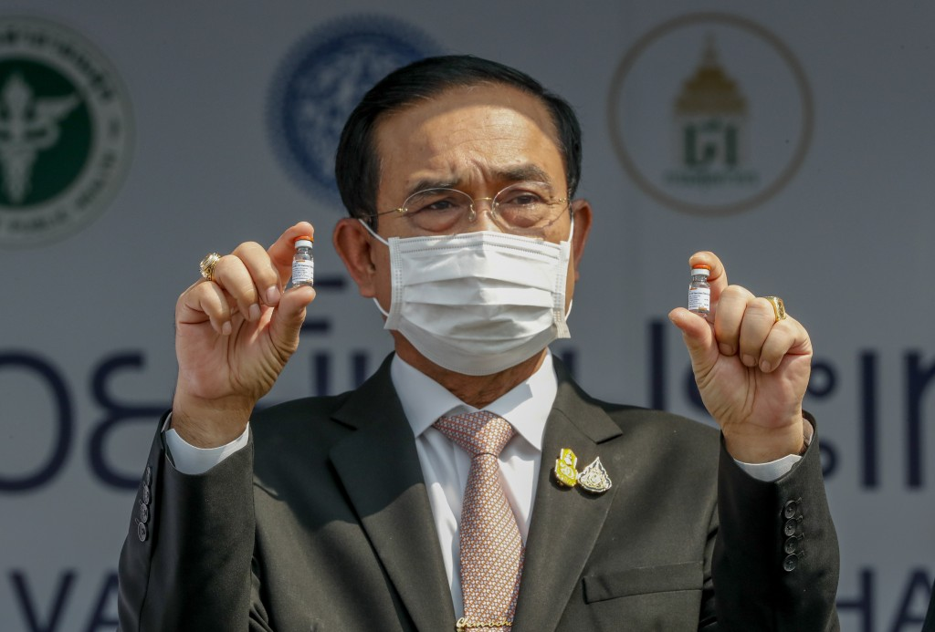 FILE - In this Feb. 24, 2021, file photo, Prime Minister Prayuth Chan-ocha holds samples of the Sinovac vaccine during a ceremony to mark the arrival ...